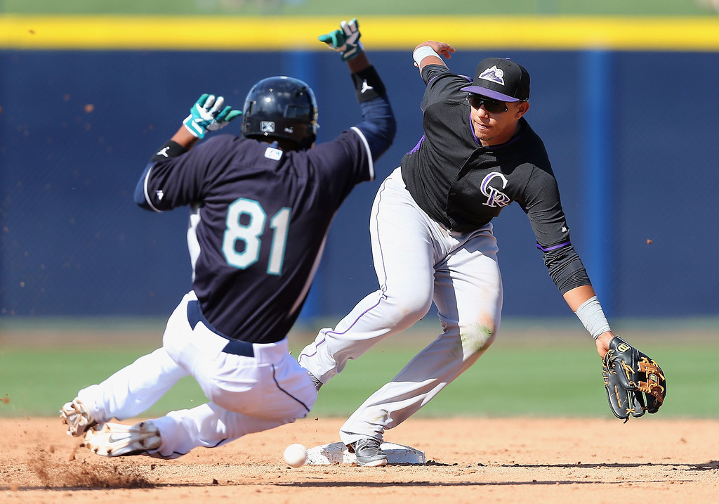 . Infielder Cristhian Adames #65 of the Colorado Rockies is unable to field the ball as Ketel Marte #81 of the Colorado Rockies steals second base during the spring training game at Peoria Stadium on March 3, 2014 in Peoria, Arizona.  (Photo by Christian Petersen/Getty Images)