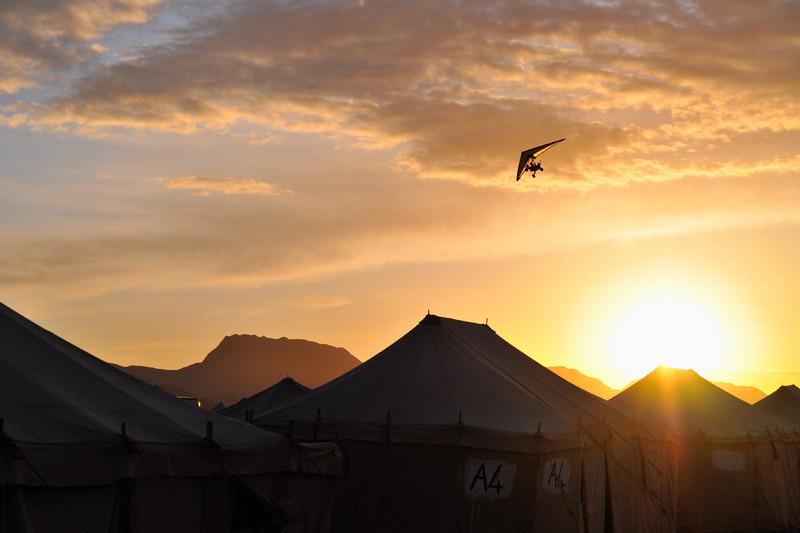 Microlight-Plane im Sonnenaufgang über dem Jabal Rum Camp im Wadi Rum. Das Wadi Rum ist eine beeindruckende Wüstenlandschaft im Süden von Jordanien, die einst die zweiten Heimat des britischen Archäologen, Geheimagenten und Schriftstellers T.E. Lawrence war (Lawrence von Arabien).