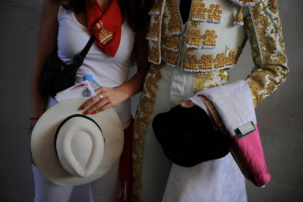 . Spanish bullfighter David Mora, right, holds his \'\'montera\'\' beside a fan before entering the bull ring at the San Fermin fiestas, in Pamplona northern Spain on Thursday, July 11, 2013. (AP Photo/Alvaro Barrientos)