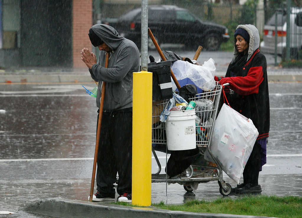 . Dorian Whittener and Brianne Martinez pause to offer a prayer in the rain along Monterey Road and West Alma Avenue in San Jose, Calif., on Thursday, Dec. 11, 2014. Whittener says they are refugees from The Jungle homeless encampment that was dismantled last week. (Gary Reyes/Bay Area News Group)