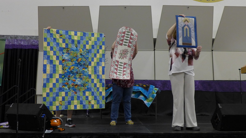 Jackie Borzich The angel quilt was made from neckties and she calls it her Executive Angel.  The middle quilt was made from a embroidery sample purchased from Country Stitches.  The quilt on the left side is a kid's quilt she is donating to the guild.