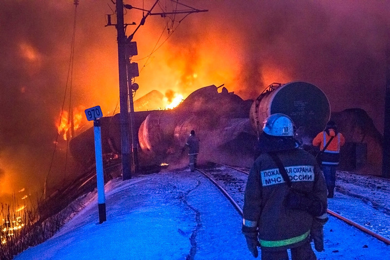 . In this photo provided by the Ministry of Emergency Situations Kirov Branch press service, firefighters watch burning tankers early Wednesday, Feb. 5, 2014, near Posdino in Kirov region of Russia, some 800 km ( about 500 miles) northeast of Moscow. 32 tankers were derailed and 12 of them burned. No casualties were reported. (AP Photo/Ministry of Emergency Situations, Kirov Branch Press Service)