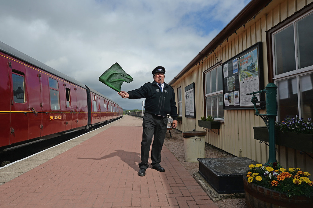 . Guard Brian Burgess waves off the 1952 British Rail Ivatt number 46512 at Strathspey Steam Railway on August 27, 2013 in Aviemore,Scotland.   (Photo by Jeff J Mitchell/Getty Images)