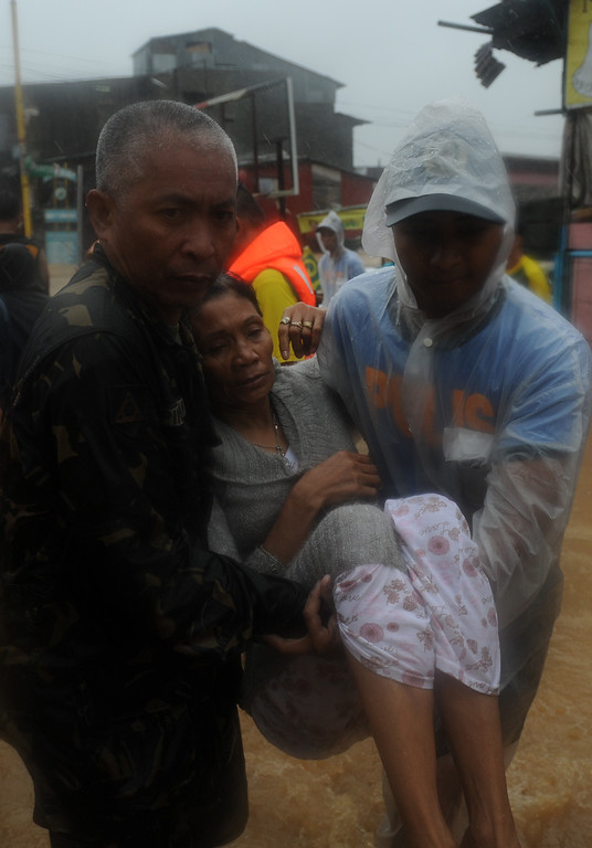 . Rescuers carry a resident after she and her family were evacuated after a river overflowed, flooding their homes due to heavy rains brought about by Tropical Storm Fung-Wong in Tumana village, Marikina City, suburban Manila on September 19, 2014. TED ALJIBE/AFP/Getty Images