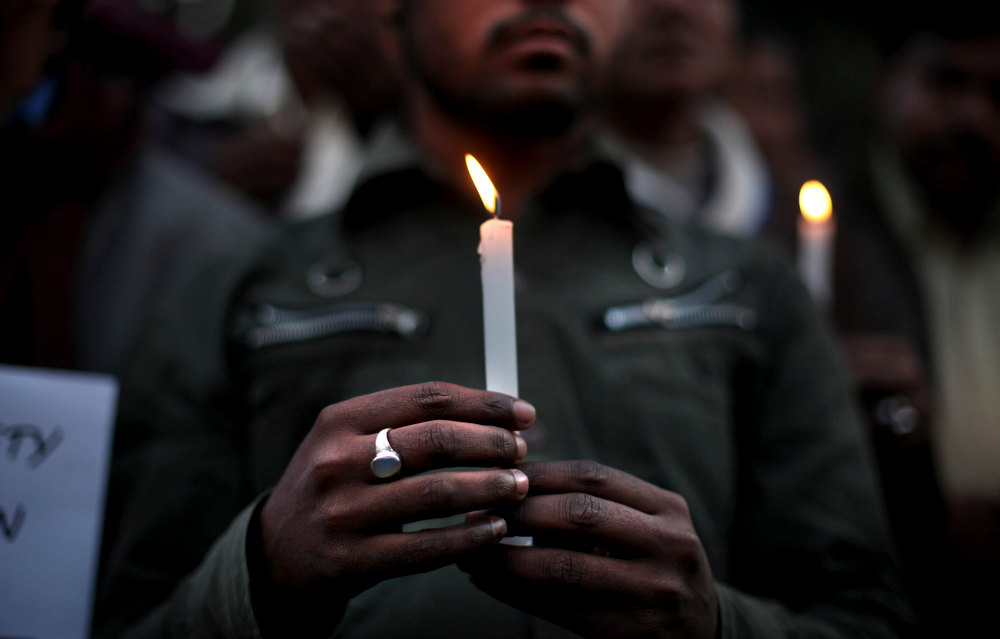 Description of . Indian people hold candles as they participate in a candlelight vigil outside the hospital where the victim of a recent rape is being treated, in New Delhi, India, Thursday, Dec. 20, 2012. The hours-long gang-rape and near-fatal beating of a 23-year-old student on a bus in New Delhi triggered outrage and anger across the country as Indians demanded action from authorities who have long ignored persistent violence and harassment against women. (AP Photo/Altaf Qadri)