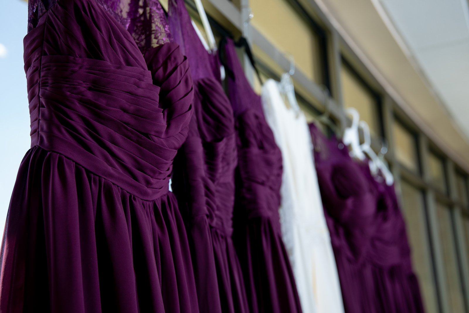 purple bridesmaids' dresses hanging on hangers next to a lace wedding dress