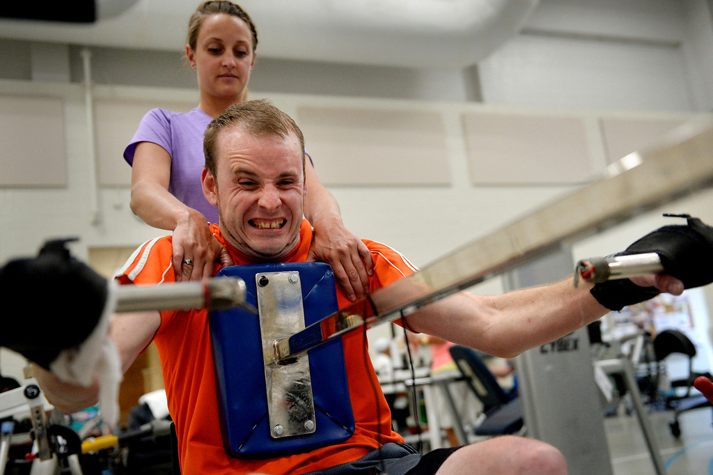 ". Therapist Shelby Allen helps James on one of Craig\'s weight machines, each designed to be easily accessible to injured clients. ""I originally gave myself three and a half years to be functional, to walk around the house with crutches, to get out of the chair. So I\'ve got a year and a half. I believe it will happen. I will not be in that damn chair.\"" (Photo By Craig F. Walker / The Denver Post)"
