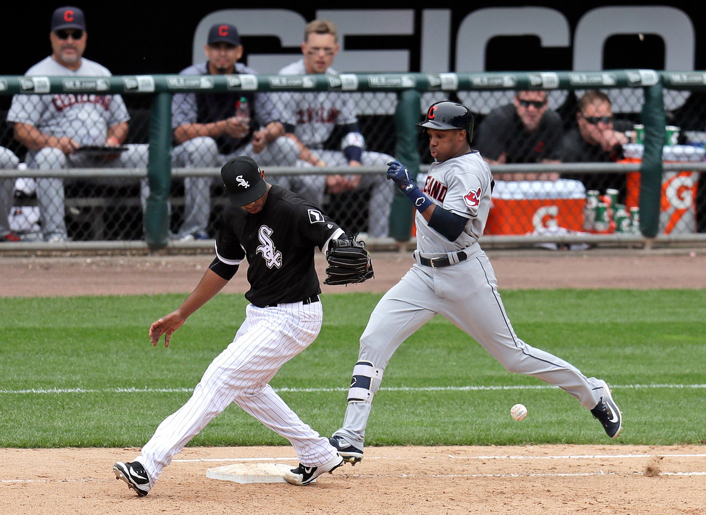 . Cleveland Indians\' Greg Allen, right, reaches first as Chicago White Sox relief pitcher Juan Minaya, left, is unable to handle the throw from first baseman Jose Abreu during the eighth inning of baseball game Thursday, June 14, 2018, in Chicago. Yan Gomes scored on the play. Minaya was charged with an error. (AP Photo/Annie Rice)