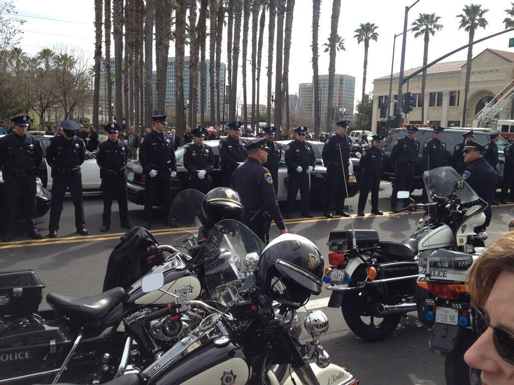 ". A silent crowd gathers as police line Autumn St. in San Jose, Calif., for the funeral services of Elizabeth Butler and Loran ""Butch\"" Baker at HP Pavilion. (Stephen Baxter/Sentinel)"
