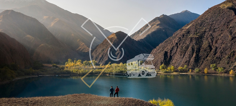 Amazing image of 2 tourists couple enjoying the Ak-Köl lake during an autumn sunrise with plenty of colors while travelling in the Kyrgyz province of Naryn