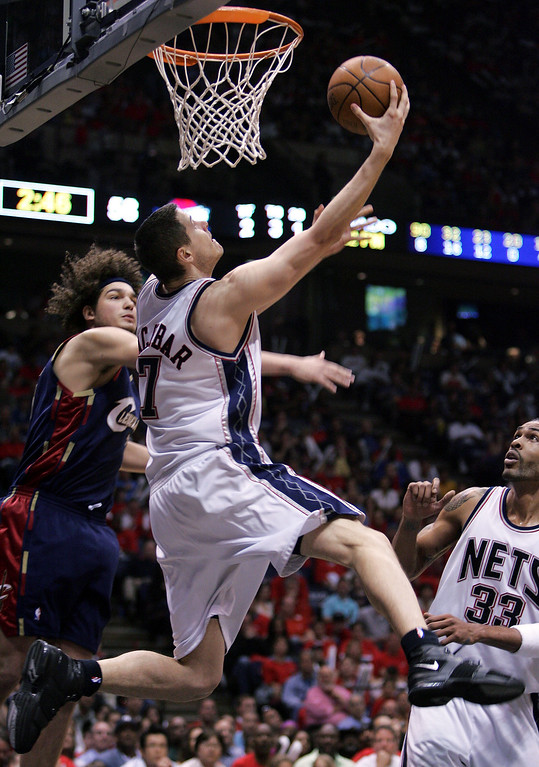 . New Jersey Nets\' Bostian Nachbar, center, of Slovenia, takes a third-period shot in front of Cleveland Cavaliers\' Anderson Varejao, left, of Brazil, during their NBA Eastern Conference semifinals game Saturday, May 12, 2007 in East Rutherford, N.J. (AP Photo/Mel Evans)