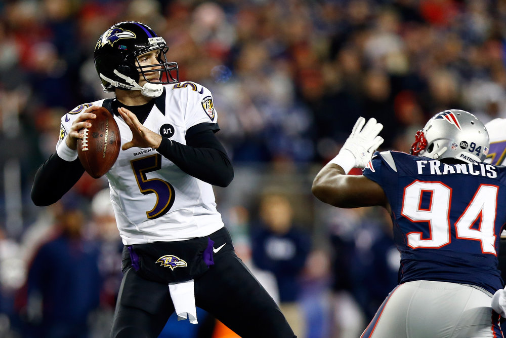 Description of . Joe Flacco #5 of the Baltimore Ravens gets pressured by Justin Francis #94 of the New England Patriots during the 2013 AFC Championship game at Gillette Stadium on January 20, 2013 in Foxboro, Massachusetts.  (Photo by Jared Wickerham/Getty Images)
