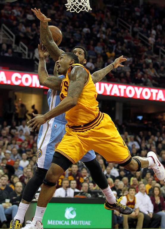 . Cleveland Cavaliers Alonzo Gee (yellow) is fouled by Denver Nuggets Wilson Chandler during the second quarter of their NBA basketball game in Cleveland, February 9, 2013.REUTERS/Aaron Josefczyk