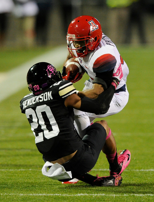 . BOULDER, CO. - OCTOBER 26: Colorado defensive back Greg Henderson (20) wrapped up Arizona tailback Ka\'Deem Carey (25) in the first half. The University of Colorado football team hosted Arizona Saturday night, October 26, 2013. Photo By Karl Gehring/The Denver Post