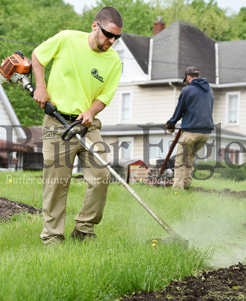 Harold Aughton/Butler Eagle: Landscapers, Shane Williams (left) and Geoff Scotts prep the Western Pennsylvania Conservancy flower beds on the island at the corner of Hansen and New Castle roads, Thursday morning, May 23.