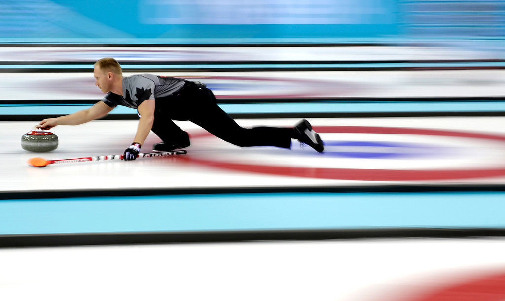 . Canada\'s skip Brad Jacobs delivers the rock during the men\'s curling competition against Denmark at the 2014 Winter Olympics, Thursday, Feb. 13, 2014, in Sochi, Russia. (AP Photo/Wong Maye-E)