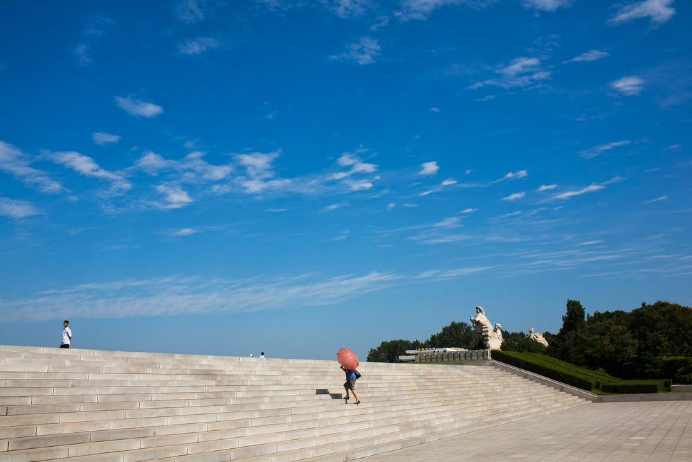 . A North Korean woman uses a parasol to protect herself from the sun as she climbs a flight of stairs in Pyongyang on Aug. 26, 2011. It\'s hard to imagine a North Korea without Kim Jong Il, who led the nation for 17 years until his death on Dec. 17, 2011. His death marks the end of an era for North Korea, which has known only two leaders: Kim and his father, Kim Il Sung. Already, a new era has begun under the leadership of his young son, Kim Jong Un.  (AP Photo/David Guttenfelder)