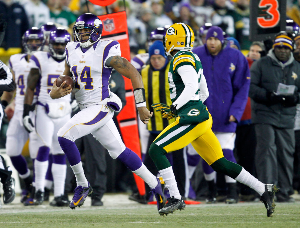 Description of . Minnesota Vikings quarterback Joe Webb (14) runs from Green Bay Packers cornerback Casey Hayward, right, during the first half of an NFL wild card playoff football game Saturday, Jan. 5, 2013, in Green Bay, Wis. (AP Photo/Mike Roemer)