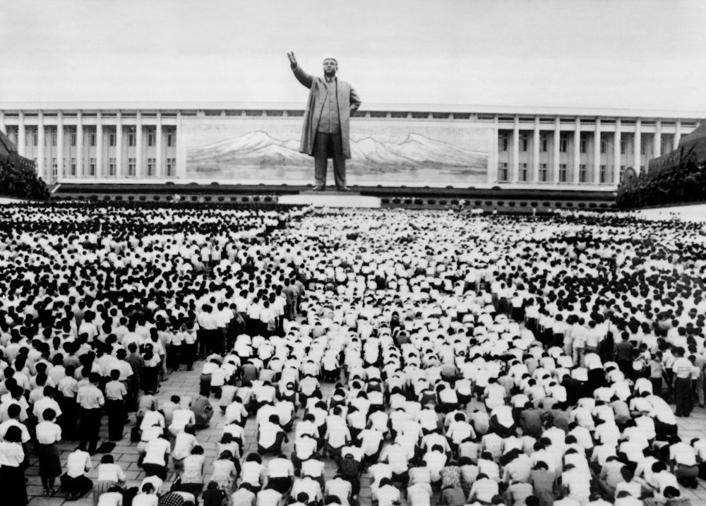 ". Thousands of people kneel down or stand in front of a giant statue (the Mansudae monument) of North Korean President Kim Il Sung to mourn the death of late President at the Korean Revolution Museum in Pyongyang, North Korea, on July 09, 1994. The late Kim died of a heart attack on July 08, after his death Kim Il-sung is named ""eternal president\"" of Democratic People\'s Republic of Korea.   (AFP/Getty Images)"