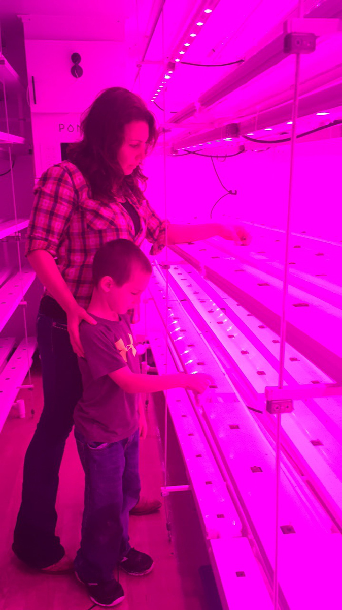 Adrienne Cloud and her son, Daniel, examine plants in a container farm.