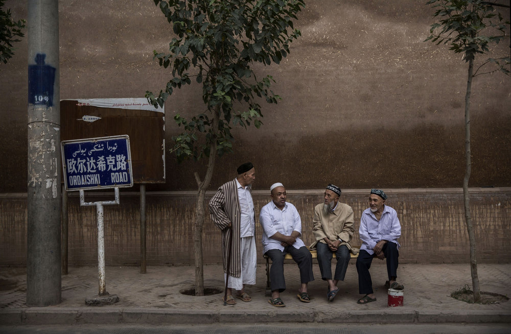 . KASHGAR, CHINA - JULY 30: Uyghur men chat before evening prayers outside a mosque on July 30, 2014 in old Kashgar, Xinjiang Province, China. Nearly 100 people have been killed in unrest in the restive Xinjiang Province in the last week in what authorities say is terrorism but advocacy groups claim is a result of a government crackdown to silence opposition to its policies. China\'s Muslim Uyghur ethnic group faces cultural and religious restrictions by the Chinese government. Beijing says it is investing heavily in the Xinjiang region but Uyghurs are increasingly dissatisfied with the influx of Han Chinese and uneven economic development.  (Photo by Kevin Frayer/Getty Images)