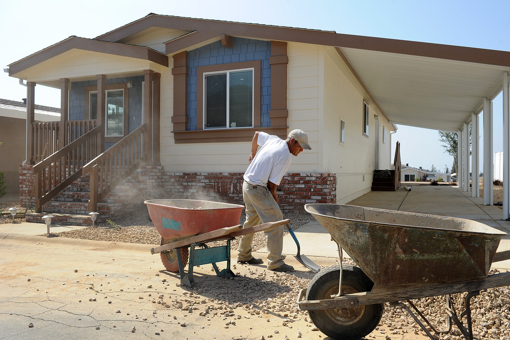 . Ofelio Verdin shovels gravel while working on the landscaping at Oakridge Mobile Home Park in Sylmar, Tuesday, April 23, 2013. (Michael Owen Baker/Staff Photographer)