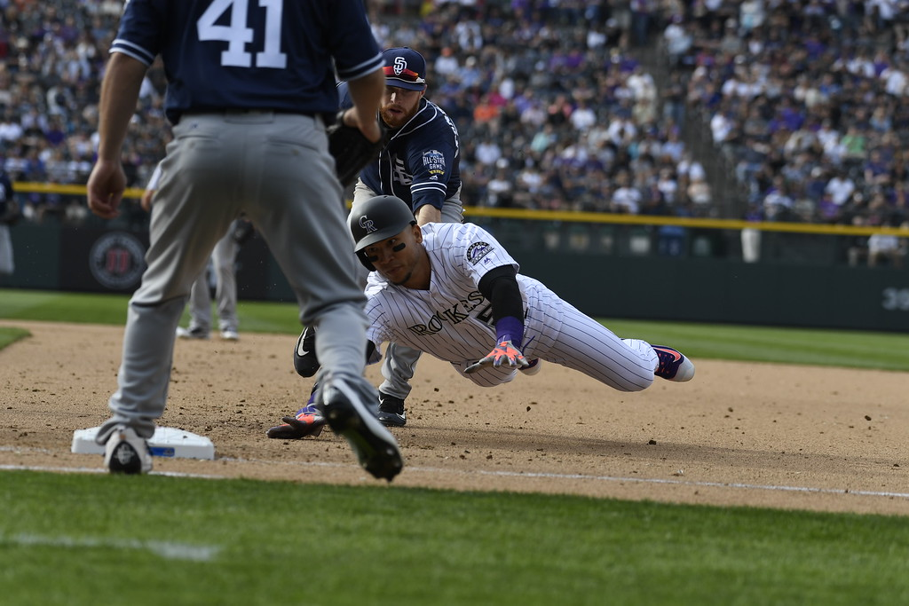 . DENVER, CO. - APRIL 08: Carlos Gonzalez (5) of the Colorado Rockies gets caught in a pickle, tagged out by Cory Spangenberg (15) of the San Diego Padres to end the seventh inning. The Colorado Rockies played the San Diego Padres Friday, April 8, 2016 on opening day at Coors Field in Denver, Colorado. (Photo By Andy Cross/The Denver Post)