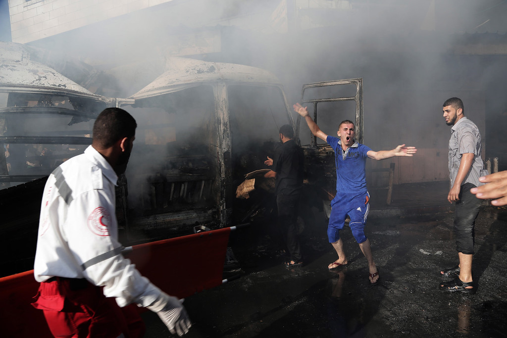 . A man shouts for help after two people were killed in an Israeli air strike on a van in Gaza City on Thursday, July 31, 2014. (AP Photo/Adel Hana)