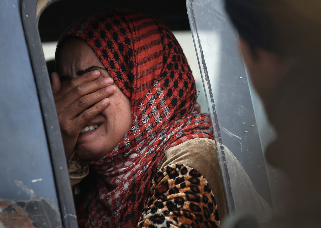 . A woman from an Arabic family cries after her family was rejected to enter a Kurdish-controlled area from an ISIS-held village on November 16, 2015 near Sinjar, Iraq. Peshmerga forces carefully screened the displaced Iraqis as they arrived, fearing enemy infiltrators and suicide bombers. The Kurdish forces, with the aid of massive U.S.-led coalition airstrikes, liberated Sinjar from ISIL extremists, known in Arabic as Daesh, moving the frontline south to Ghabosyeh. About a thousand villagers from Ghabosyeh fled north to Kurdish held territory, to take refuge in camps or onward as refugees to Turkey or Europe.  (Photo by John Moore/Getty Images)