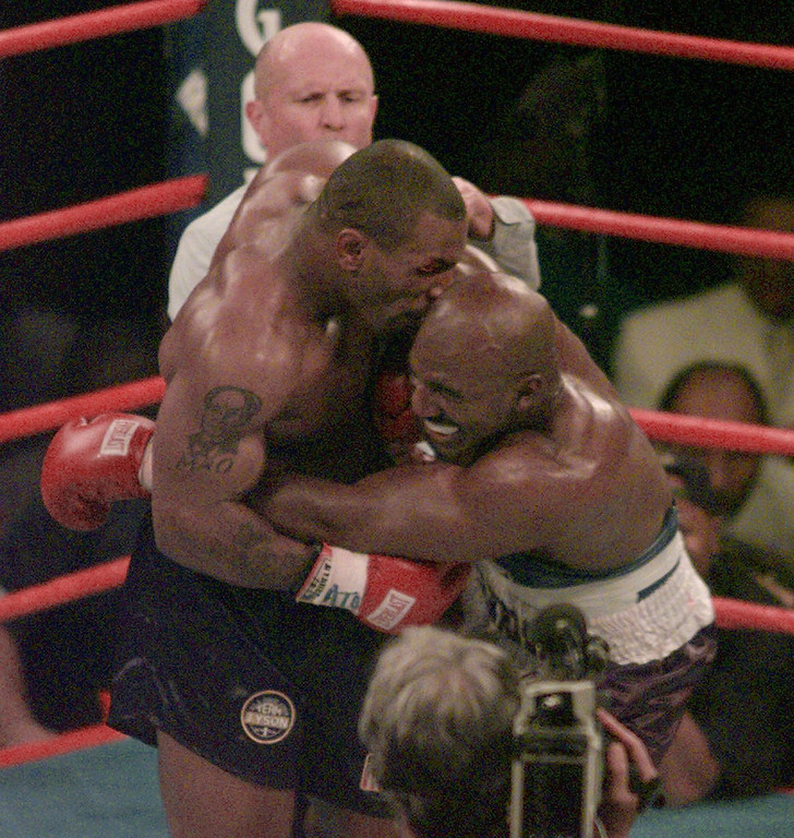 ". FILE -- This is a June 28, 1997, file photo showing Mike Tyson biting into the ear of Evander Holyfield in the third round of their WBA heavyweight bout in Las Vegas. Tyson and Holyfield are expected to appear Friday, Oct. 16, 2009, on ""The Opray Winfrey Show\"" from Chicago. (AP Photo/Jack Smith, File)"