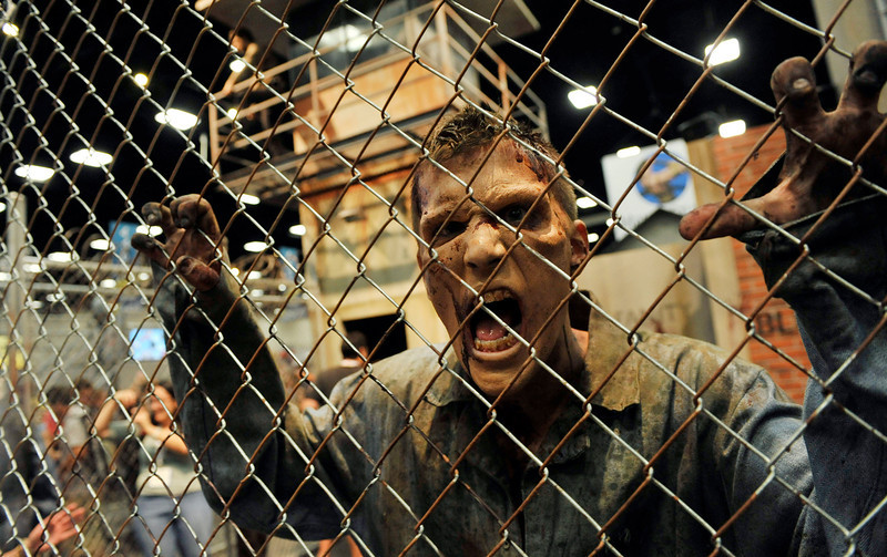 ". A zombie character in an exhibit inspired by the television series ""The Walking Dead\"" screams at onlookers during the Preview Night event on Day 1 of the 2013 Comic-Con International Convention on Wednesday, July 17, 2013 in San Diego, Calif. (Photo by Chris Pizzello/Invision/AP)"