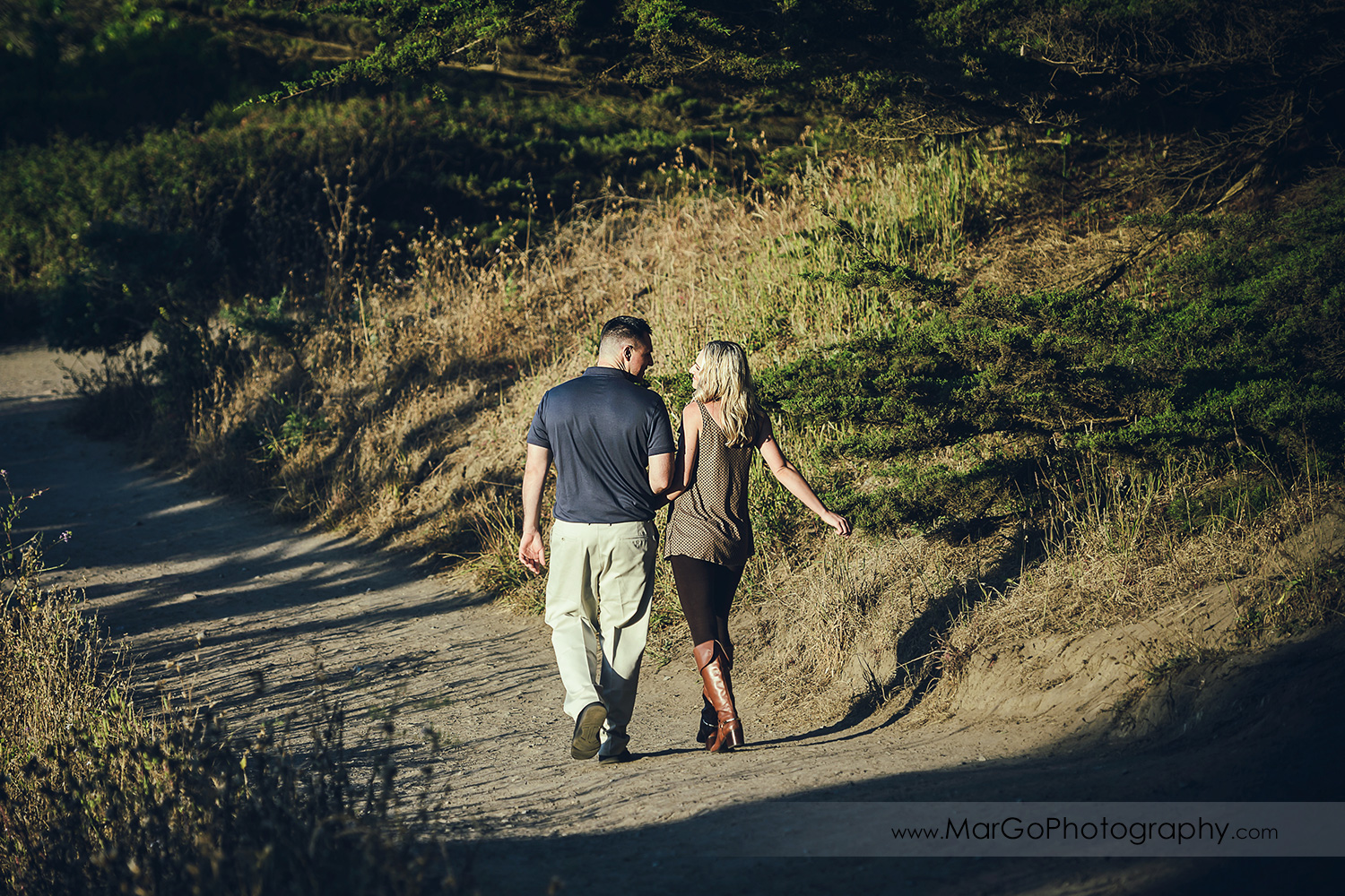 man in navy blue shirt and woman in brown tunic holding hands and walking during engagement session at San Francisco Lands End