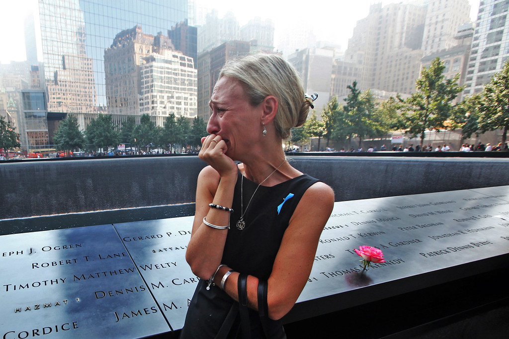 . Carrie Bergonia of Pennsylvania looks over the name of her fiance, firefighter Joseph Ogren at the 9/11 Memorial during ceremonies for the twelfth anniversary of the terrorist attacks on lower Manhattan at the World Trade Center site on September 11, 2013 in New York City.  (Photo by Chris Pedota-Pool/Getty Images)