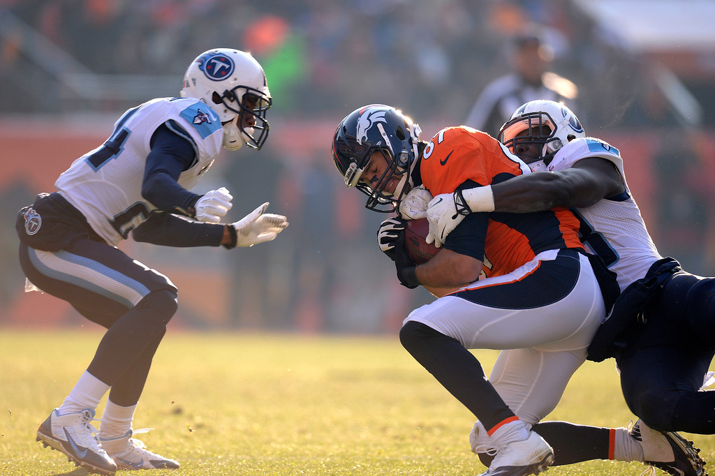 . Denver Broncos wide receiver Eric Decker (87) is tackled by Tennessee Titans middle linebacker Moise Fokou (53) and Tennessee Titans cornerback Coty Sensabaugh (24). (Photo by John Leyba/The Denver Post)