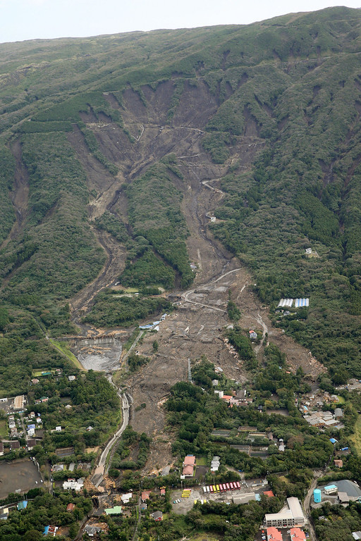 . Houses in a residential area in Oshima are buried by mudslides after a powerful typhoon hit Izu Oshima island, about 120 kilometers (75 miles) south of Tokyo Wednesday morning, Oct. 16, 2013.  (AP Photo/Kyodo News)