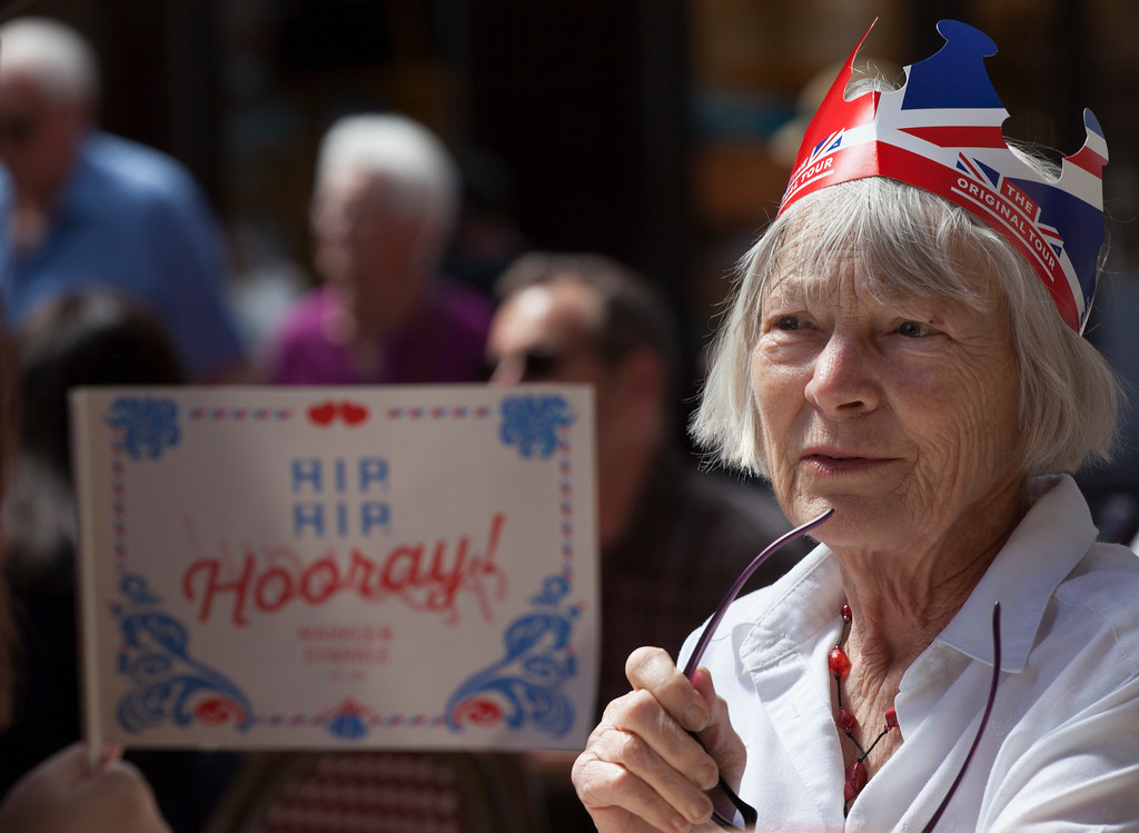 ". A woman looks up to a person holding a small flag reading ""Hip Hip Hooray\"" as they sit on a terrace near Windsor castle, England, Friday, May 18, 2018. Preparations continue in Windsor ahead of the royal wedding of Britain\'s Prince Harry and Meghan Markle Saturday May 19. (AP Photo/Peter Dejong)"