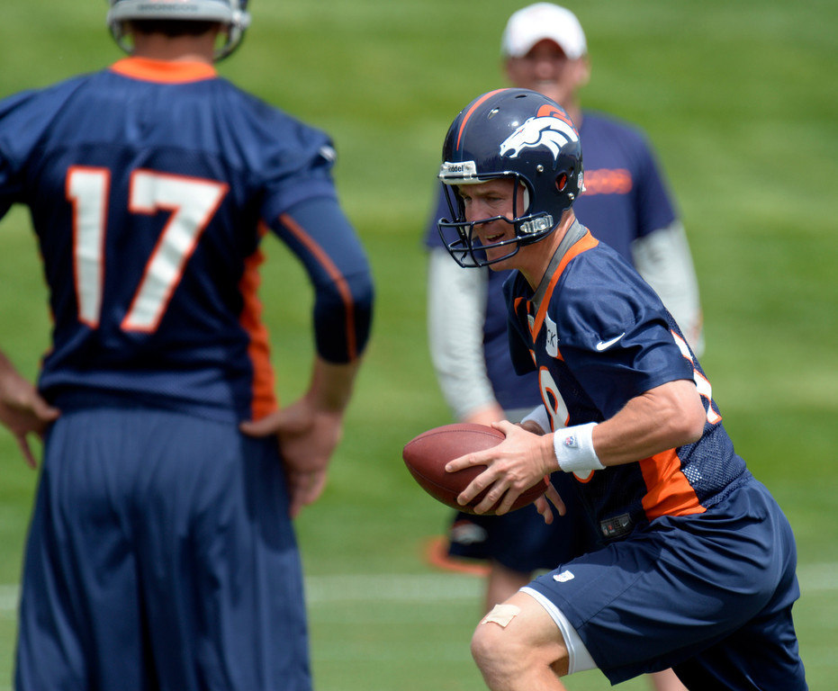 . Peyton Manning (18) quarterback  of the Denver Broncos runs through drills during drills at mini camp June 12, 2013 at Dove Valley. (Photo By John Leyba/The Denver Post)