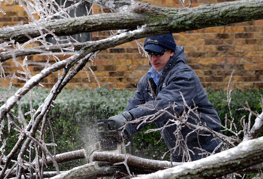 . Stephen Lanning, a city of Richardson, employee uses a chain saw to cut limbs from a ice covered tree that fell across a neighborhood intersection, Friday, Dec. 6, 2013, in Richardson, Texas. (AP Photo/Tony Gutierrez)