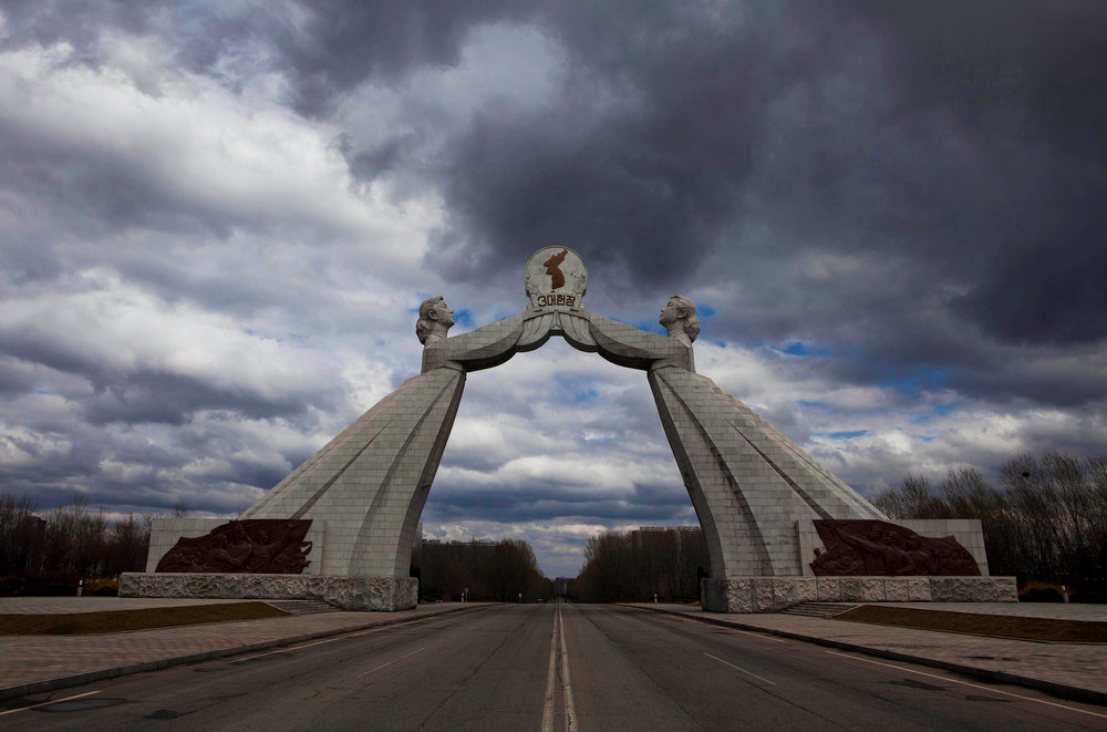 Description of . A statue known as the Monument to the Three Charters for National Reunification, which symbolizes the hope for eventual reunification of the two Koreas, arches over a highway at the edge of Pyongyang, North Korea on April 18, 2011.  (AP Photo/David Guttenfelder)