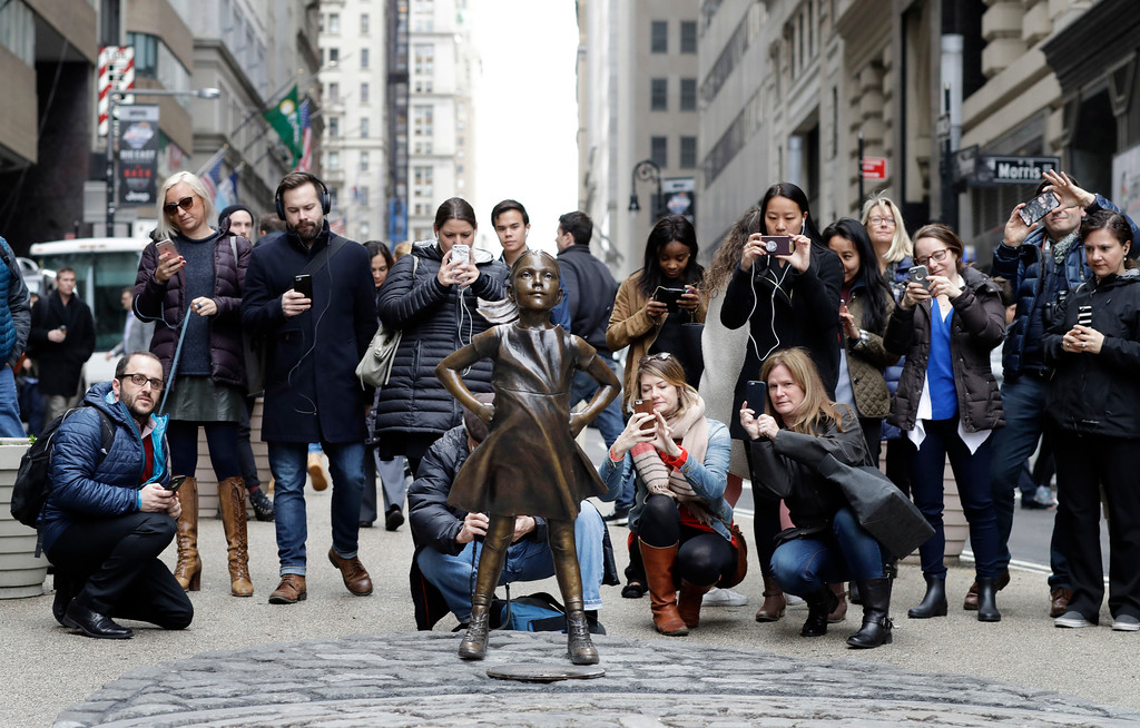 ". In this March 8, 2017, a crowd gathers around the ""Fearless Girl\"" statue in New York. It took months of intricate planning by two corporate giants to install the statue facing charging bull statue in lower Manhattan under the veil of darkness in time for Wednesday\'s International Women\'s Day. The one-week permit for the installation downtown was extended by New York Mayor Bill de Blasio through April 2 and popular support for the piece to be kept permanently is growing, with petitions being signed. (AP Photo/Mark Lennihan)"