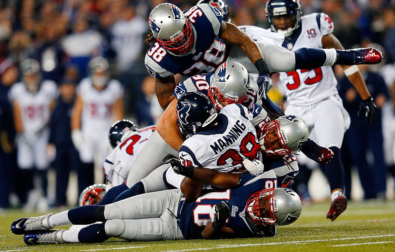 . Danieal Manning #38 of the Houston Texans gets tackled by Matthew Slater #18, Niko Koutouvides #90, Marquice Cole #23, and Brandon Bolden #38 of the New England Patriots during the 2013 AFC Divisional Playoffs game at Gillette Stadium on January 13, 2013 in Foxboro, Massachusetts.  (Photo by Jim Rogash/Getty Images)