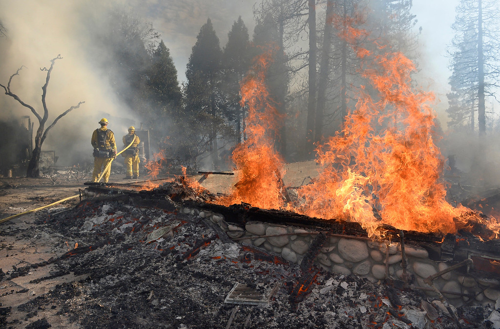 . Firefighters douse flames from an outbuilding next to a structure that burned on Cedar Drive in Oakhurst, Calif., Sunday, Sept. 14, 2014, as two raging wildfires in the state forced hundreds of people to evacuate their homes. The California Department of Forestry and Fire Protection said flames damaged or destroyed 21 structures. The Fresno Bee reports one neighborhood was hit especially hard, with several homes turned to ash and smoldering embers. (AP Photo/The Fresno Bee, Mark Crosse)