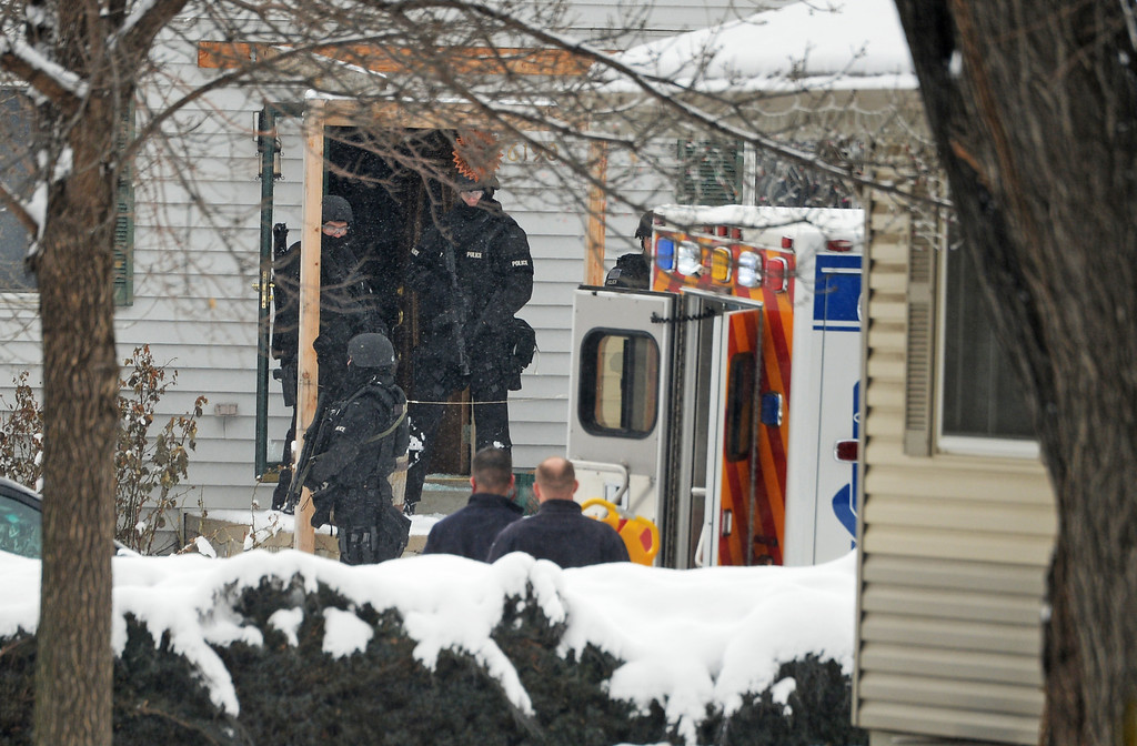 . Police rush into a home in Arvada during a hostage situation, February, 04 2014. There is heavy police and SWAT presence in the 6100 block of Grey Street, and surrounding homes have been evacuated. (Photo by RJ Sangosti/The Denver Post)