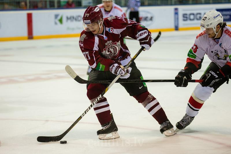 Marcel Hascak (77) mēģina nosargāt ripu no Traktor Chelyabinsk hokejista Chistov Stanislav (23)