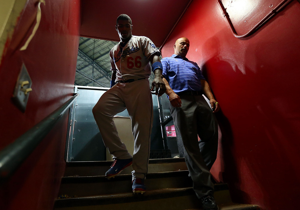 . PHOENIX, AZ - JULY 10:  Yasiel Puig #66 of the Los Angeles Dodgers walks back to the clubhouse after defeating the Arizona Diamondbacks in the 14th inning of the MLB game at Chase Field on July 10, 2013 in Phoenix, Arizona. The Dodgers defeated the Diamondbacks 7-5 in 14 innings.  (Photo by Christian Petersen/Getty Images)