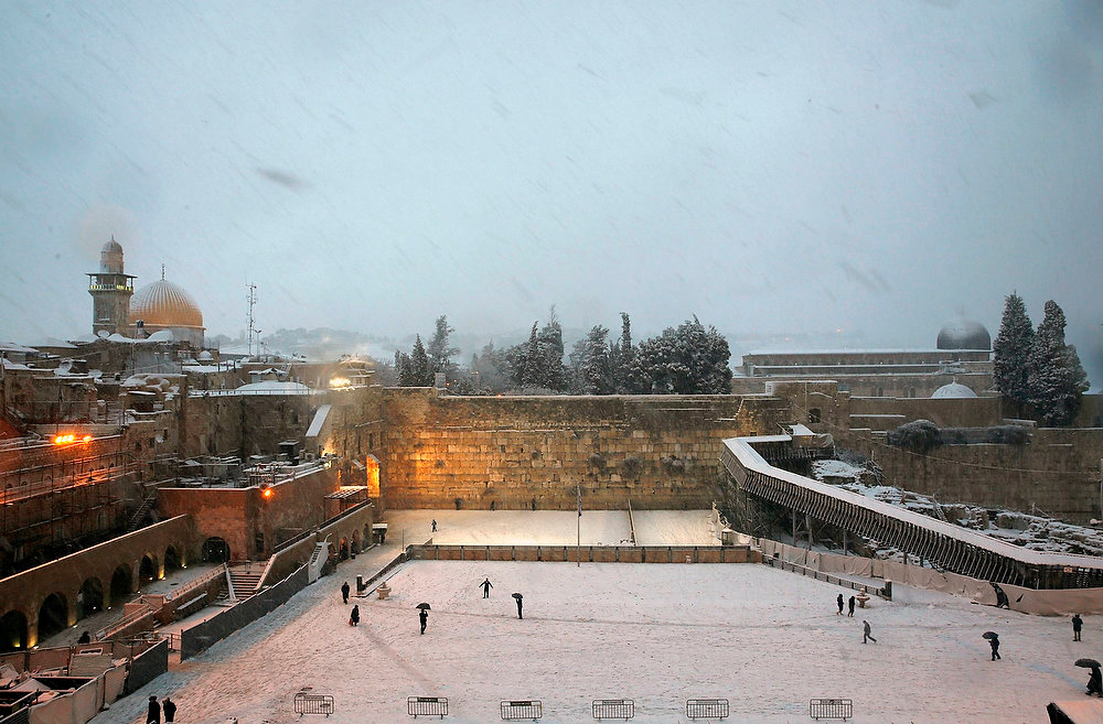 . People walk in front of the Western Wall and Dome of the Rock (L) as snow falls in Jerusalem\'s Old City January 10, 2013.  The worst snowstorm in 20 years shut public transport, roads and schools in Jerusalem on Thursday and along the northern Israeli region bordering on Lebanon. REUTERS/Darren Whiteside