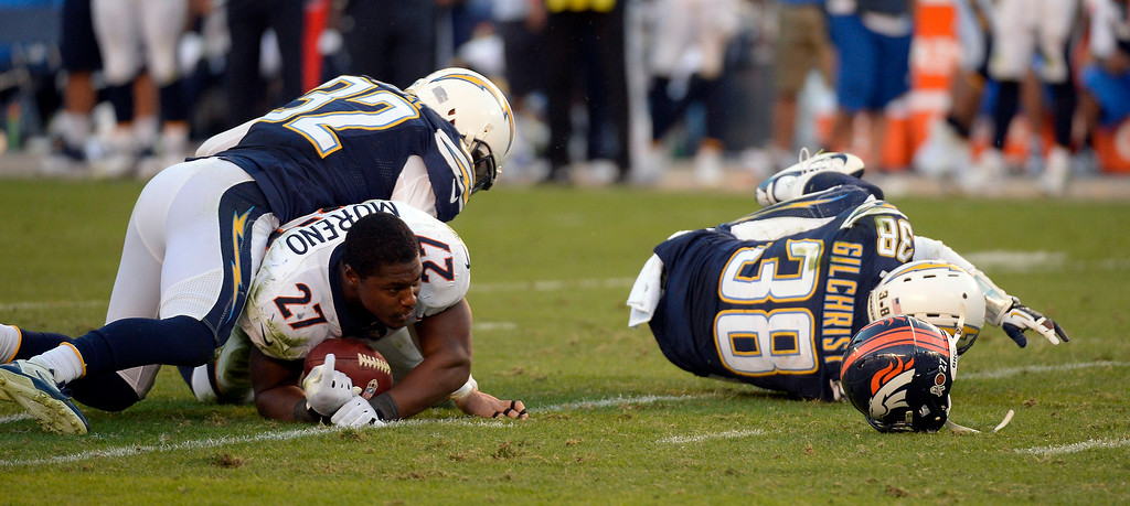 . SAN DIEGO, CA - NOVEMBER 11: Denver Broncos running back Knowshon Moreno (27) loses his helmet after getting tackled by San Diego Chargers free safety Eric Weddle (32) during the fourth quarter at Qualcomm Stadium. (Photo by John Leyba/The Denver Post)