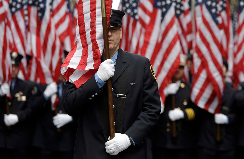 . Firefighters carrying 343 American flags representing each of their colleagues who died during the terrorist attacks on the World Trade Center, march up Fifth Ave. during the St. Patrick\'s Day Parade, Tuesday, March 17, 2015, in New York.  (AP Photo/Mary Altaffer)