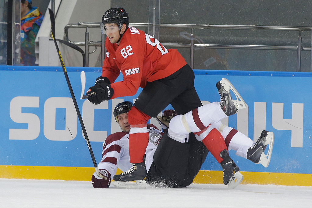 . Switzerland forward Simon Moser gets tangled up with Latvia defenseman Sandis Ozolins during the first period of the 2014 Winter Olympics men\'s ice hockey game at Shayba Arena, Wednesday, Feb. 12, 2014, in Sochi, Russia. (AP Photo/Matt Slocum)