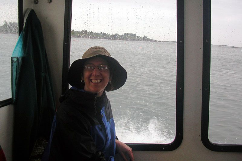 """Rain fell hard this last night of our trip, and with an 8 mile open water crossing staring us in the face, we opted for the """"find a lobsterman to take us home"""" option.  (Cash will get you anything in large enough quantities)  Susan is flashing that smile that only comes with the anticipation of a hot shower."""